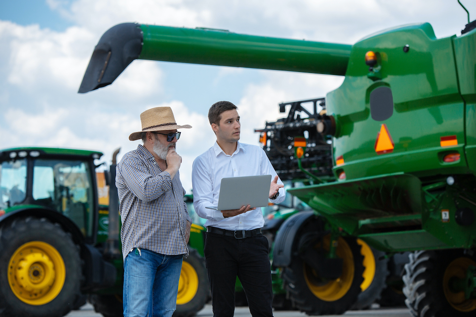Professional farmer with a modern combine at field in sunlight at work. Confident, bright summer colors. Agriculture, exhibition, machinery, plant production. Senior man near his tractor with investor.