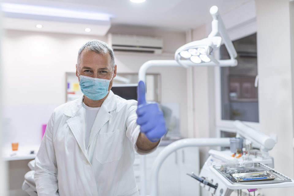Smiling male dentist showing thumbs up over medical office background. Happy middle aged male dentist in white coat showing thumbs up at dental clinic office. Healthcare, profession, stomatology and medicine concept.