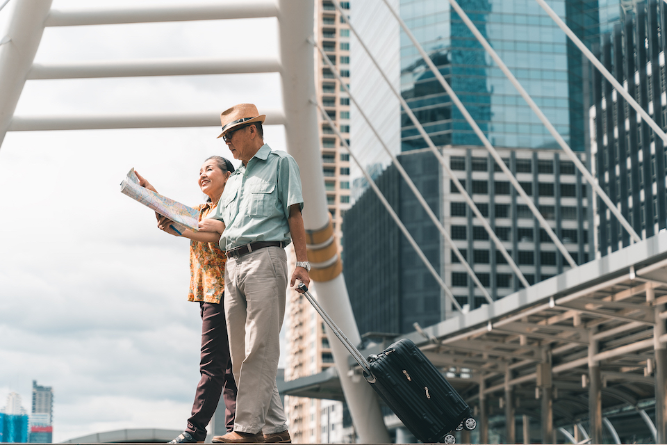 A couple of elderly Asian tourists visiting the capital happily and having fun and looking at the map to find places to visit.