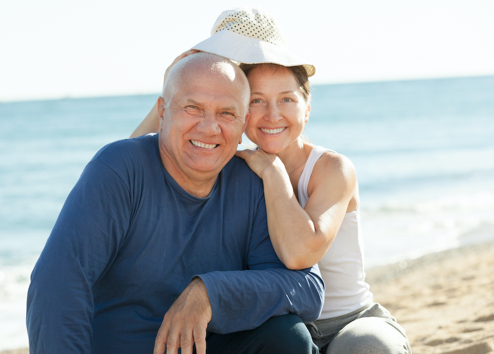 Happy mature couple together at sea sandy beach