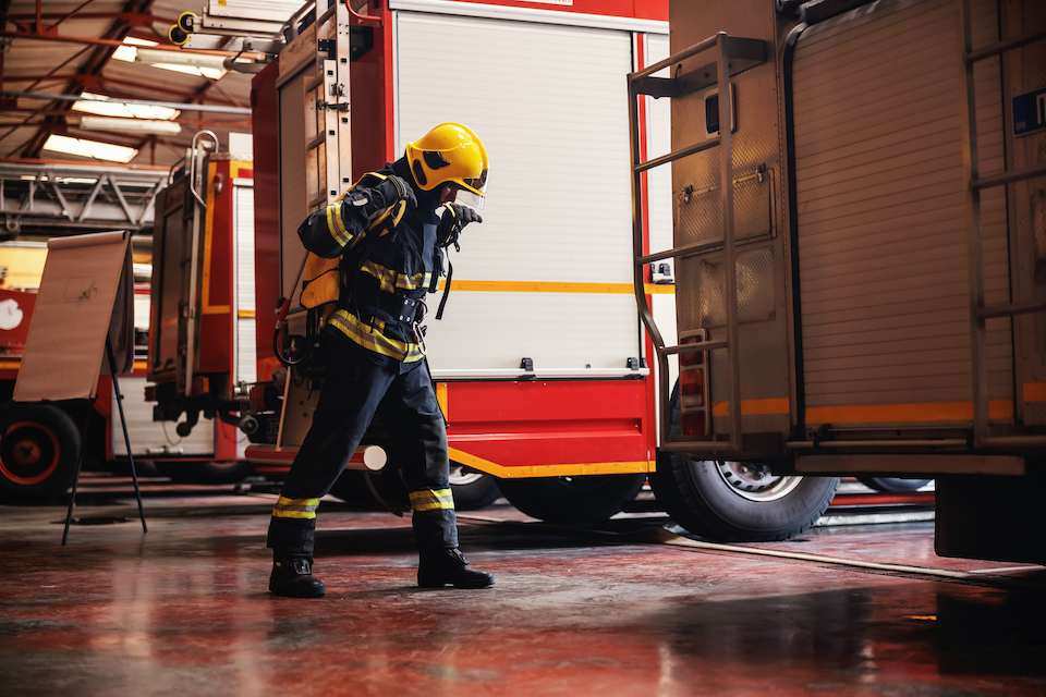 Full length of brave fireman standing in fire station in full protective uniform and preparing for action.
