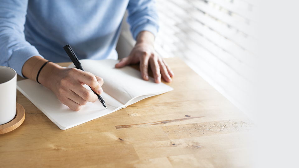 Man writing in a journal while at home in the new normal
