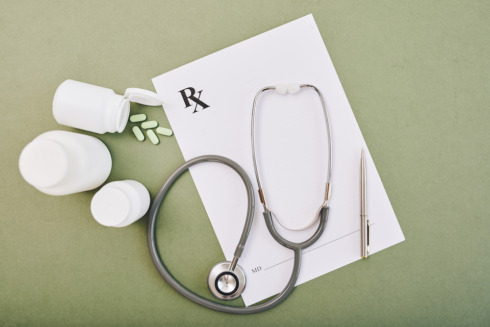 Stethoscope, blank prescription form and tablets on table