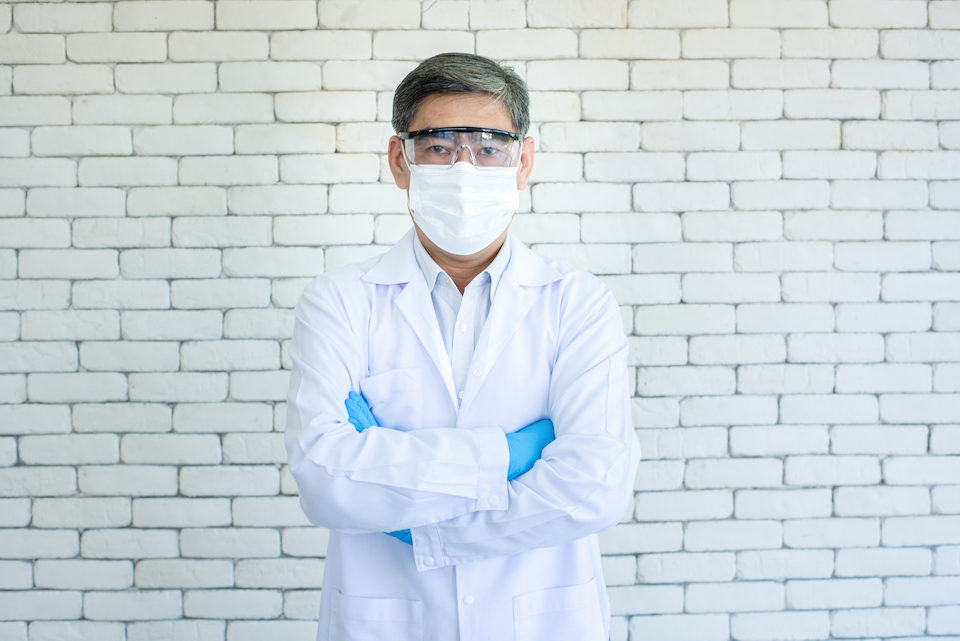 Portrait of Asian elder doctor or researcher wear lab coat, clear eyeglasses and face mask standing and arm crossed with white brick background.