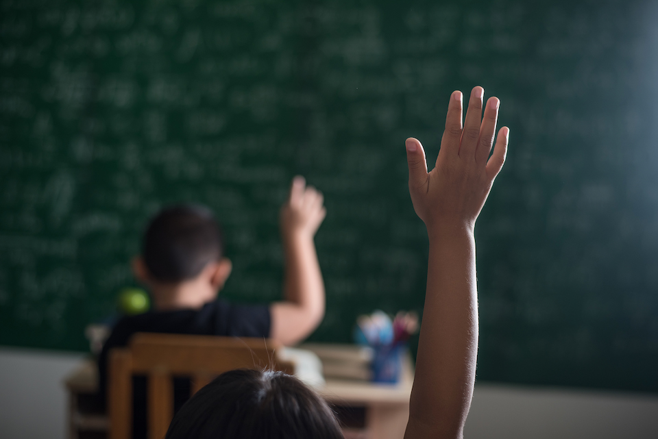 kid raising his hand in classroom