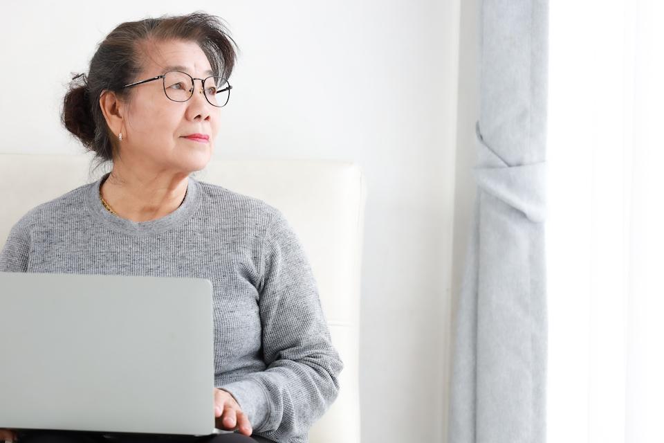 Asian Senior woman retirement using laptop computer in living room